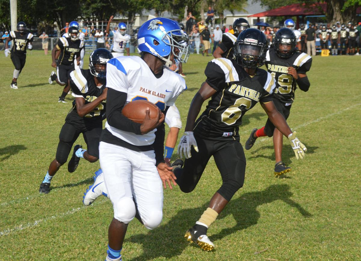 Palm Glades's Darius Hunter-Henley (82) carrying the ball while Everglades Prep's Ja'maree Thomas (6) is looking to make a tackle