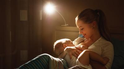 breastfeeding. mother feeding a baby breast in bed dark night