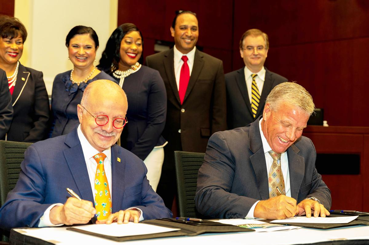 Homestead Vice-Mayor Jon Burgess and Dr. Eduardo Padron, President, MDC, were all smiles in signing the property transfer  for the new Student Success Center. Back, left to right: Dr. Jeanne F. Jacobs, President, Homestead and West Campus,  Dr. Lenore Rodicio, MDC Executive Vice President and Provost, Councilmember Patricia Fairclough, Councilmember Elvis Maldonado, City Manager George Gretsas.