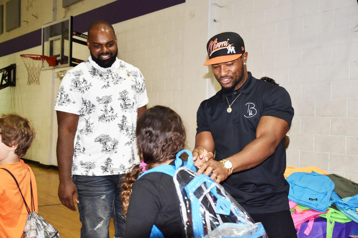 Oher and Sanford give a  backpack and encouragement to a student.