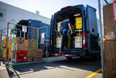 An Amazon delivery van loads up an Amazon Delivery Station.