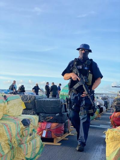 Coast Guard Petty Officer 2nd Class Jonathan Ayers guards approximately 11,500 pounds of interdicted  cocaine and approximately 17,000 pounds of interdicted marijuana, Aug. 27, 2020, Port Everglades, Florida.