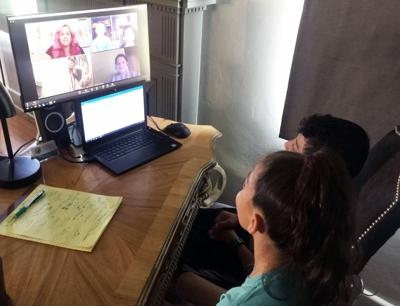 Students participate in an online classroom to complete school  assignments from home.