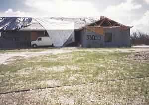 The Meneses' home after the hurricane. Roof-windows-shrubbery gone, rock-wind-water damage.