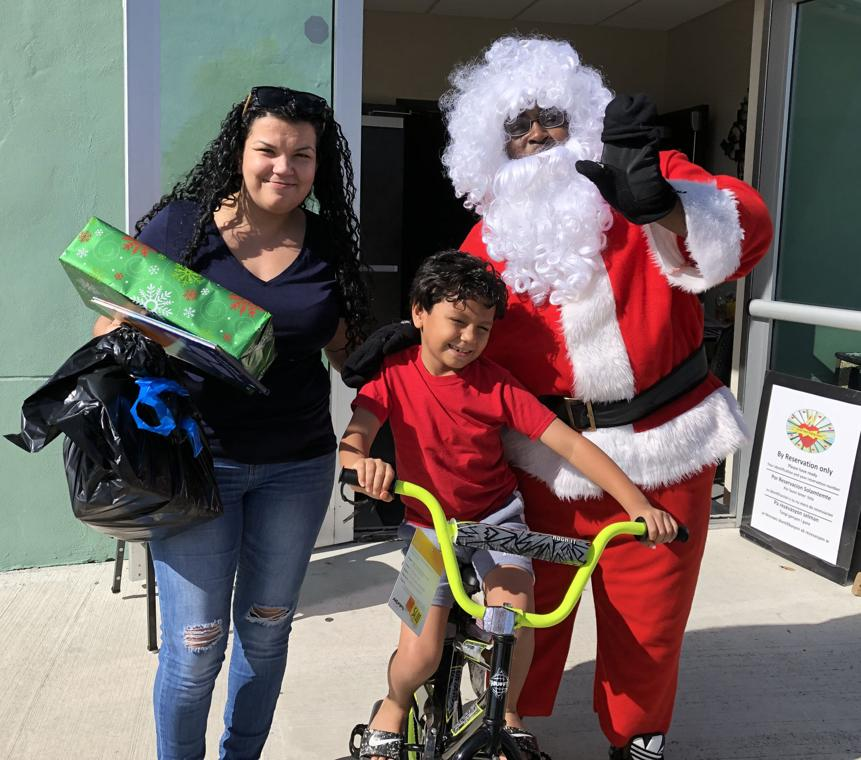 Santa brings a new bicycle for a happy little boy.