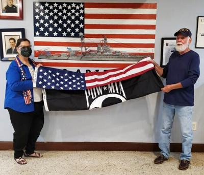 :  Jody Nerney, VFW Auxiliary District President presents an American flag and POW flag to U.S. Naval Veteran, Allen Kasmir of Homestead.  Allen served as a submariner aboard the USS Chopper SS342.