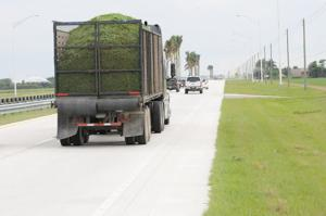 After - a truck hauls a load of beans along a section of completed highway closer to Bird Road