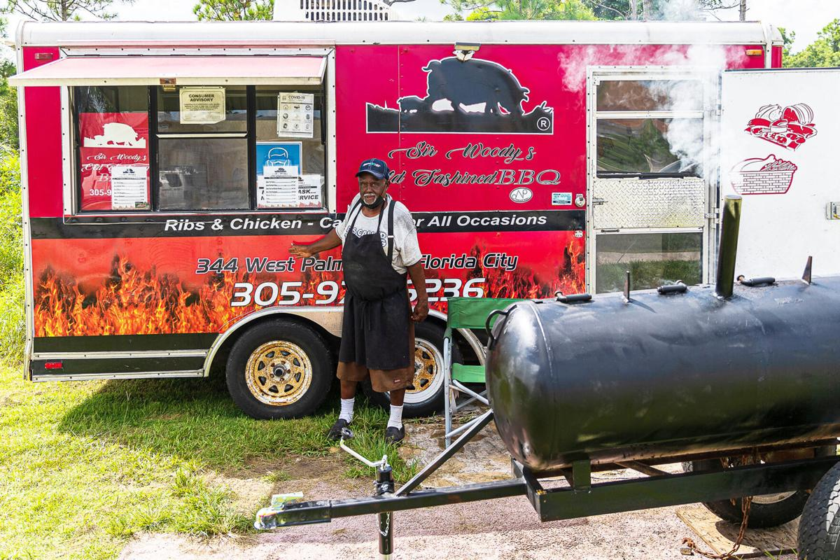 Sir Woody stands by his serving trailer and much smaller replacement pit at the spot he has been  cooking barbeque for almost 24 years.