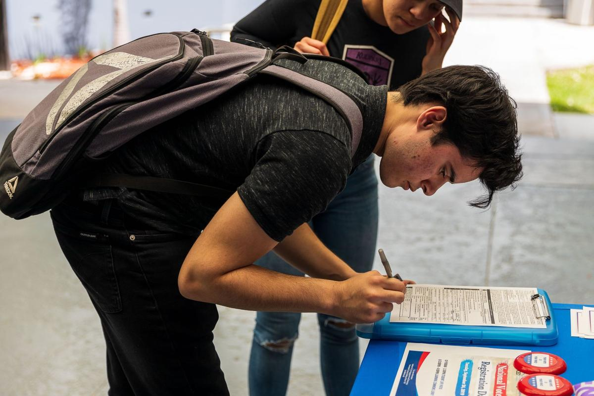 Daniel Gonzalez a freshman from Homestead concentrated on filling out his Voter Registration Application.