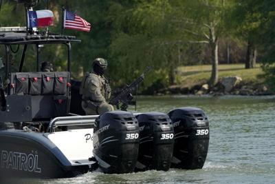 A Texas Department of Public Safety officer is seen on a boat while patrolling the U.S.-Mexico border, March 23, 2021, in Mission, Texas.