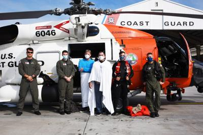 Coast Guard MH-60 Jayhawk helicopter crew pose with two men rescued by the crew, Dec. 12, 2020. Dennis Amo and Larry Mccain were rescued after their boat took on water 40 miles west of Bradenton, Florida.