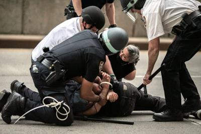 Police arrest protesters refusing to get off the streets during an imposed curfew while marching in a solidarity rally over the death of George Floyd, June 2, 2020, in New York.