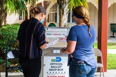 A Poll Worker checks Myra Reys' ID and absentee ballot Monday  afternoon in Homestead.
