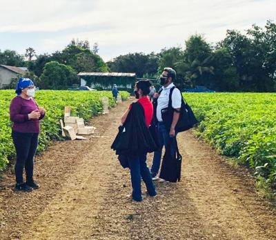 Sifuentes Farms Crew Leader Blanca Rivas talks with MUJER staff members Christina Aldana and Saul Aleman while they wait for farm workers to gather.