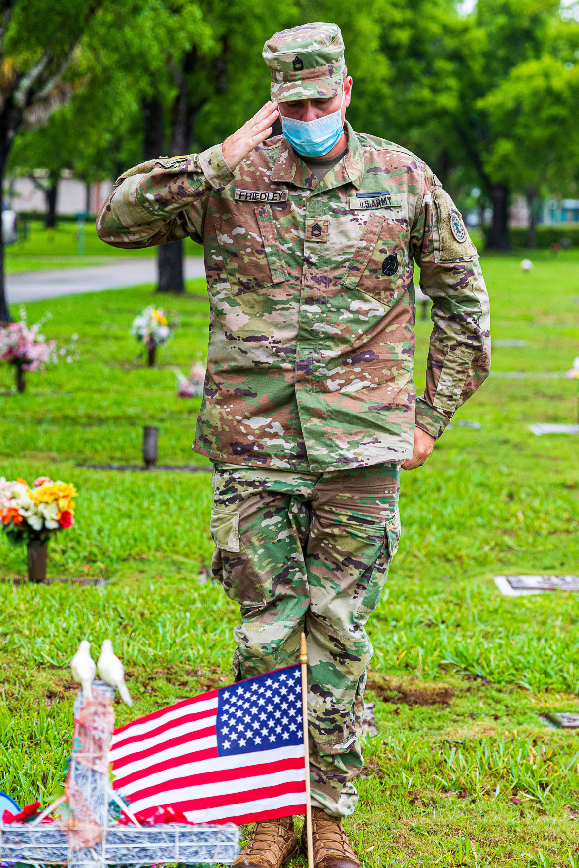 SFC Matthew Friedley of the Miami Recruiting Battalion salutes after placing a flag on the grave of World War II Veteran Rito Velez.