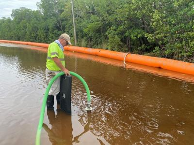 Foreman Montello Desquotte helps U.S. Flood Control fill the barriers in the Twin Lakes community to help keep the king tide from coming into the road.