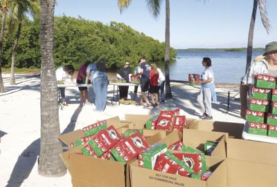 Filling Christmas Child Shoeboxes on the beach at John Pennecamp Park