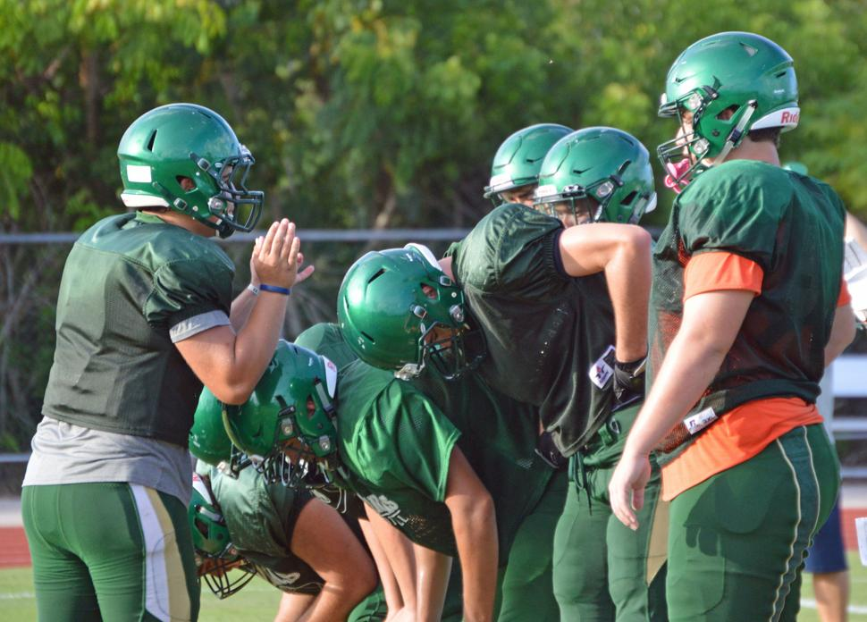 Greg Penton, to the left, huddling with the offense.
