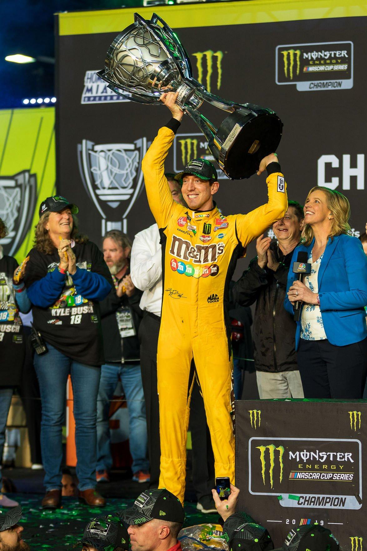 Kyle Busch hoists the championship trophy.  Photo: Hugh Hudson