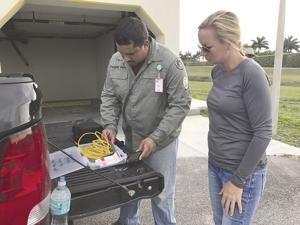 Python Hunter Omar Gomez and Rep. Holly Raschein check equipment before going out on python hunt.