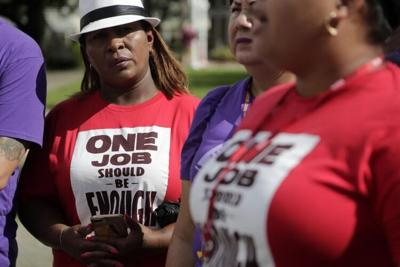 """A woman wears a T-shirt reading, """"One Job Should be Enough,"""" during a rally calling for an increase to the minimum wage in Miami."""