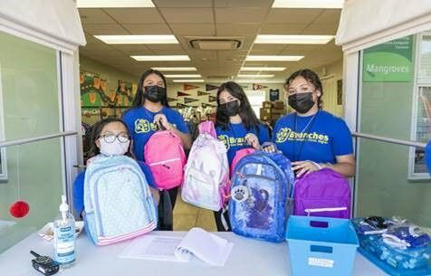 """Volunteers, who are the Branches """"Climb"""" program students in high school and middle school who want to serve the community, hold up backpacks filled with school supplies"""