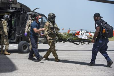 Medical volunteers and aircrew with the 1st Battalion, 228th Aviation Regiment, Soto Cano Air Base, Honduras, unload patients from a helicopter during a medical evacuation mission at Port-au-Prince, Haiti, Aug. 24, 2021