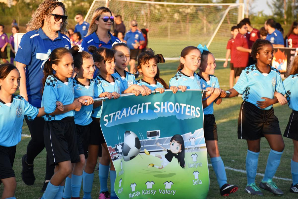 One of the many AYSO teams parading onto their new fields.