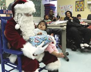 Santa gives a  present to a patient at PATCHES Prescribed Pediatrics Extended Care.