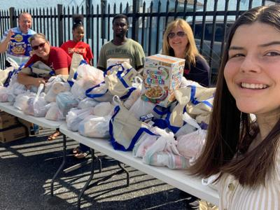 Cheerful Homestead Outreach Team volunteers smile after putting together another large group of meal packs  to be delivered.