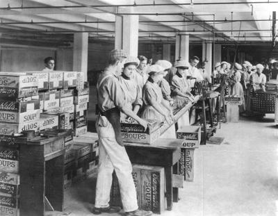 Workers label and pack cans for distribution, c. 1905