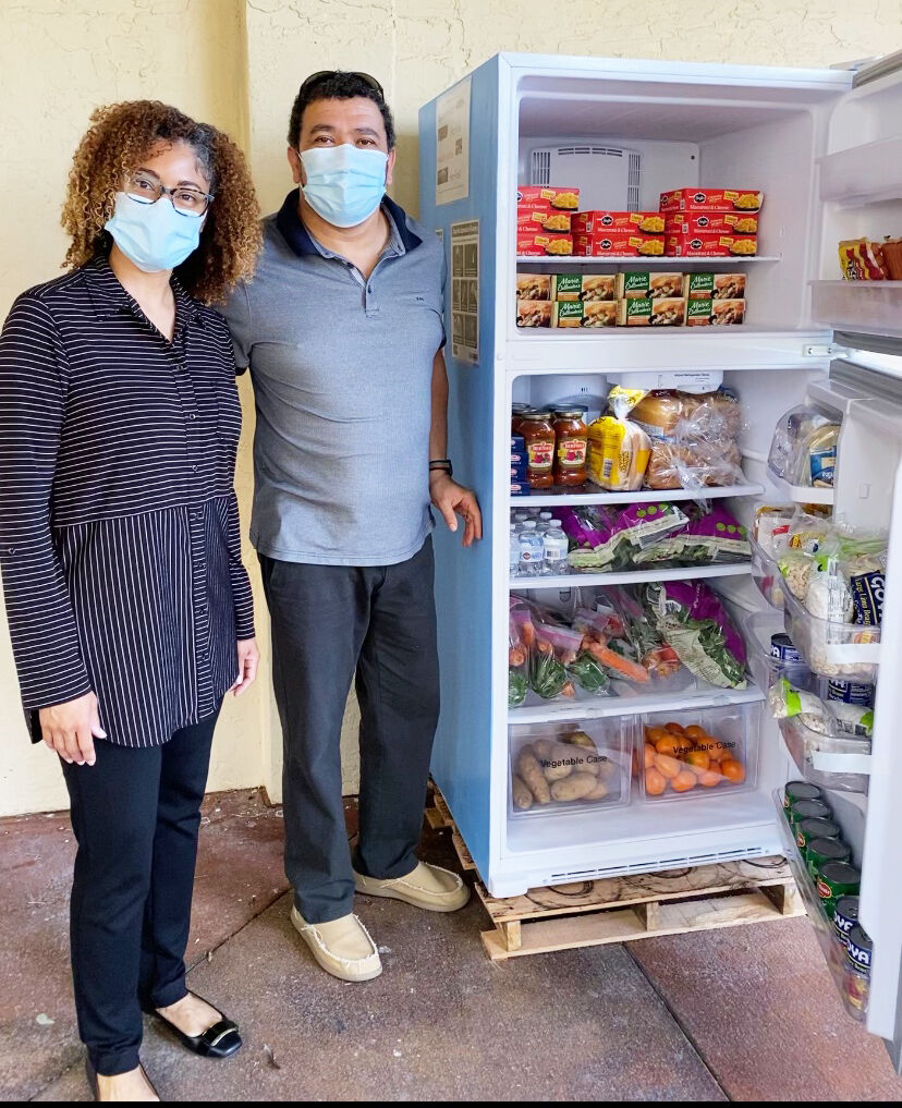 From left: Tamu and Eldred Fourie show the filled  Community Fridge.