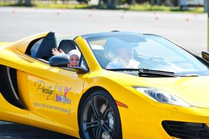 A young girl enjoying her ride in an exotic car with Ride2Revive.