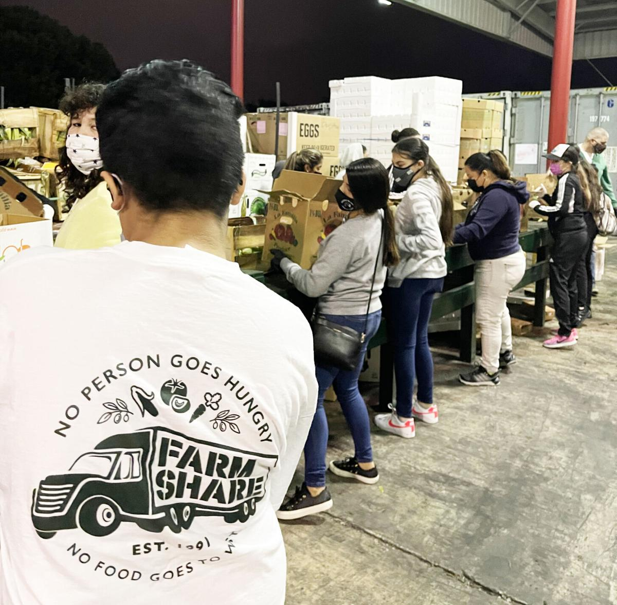 Farm Share volunteers loading up boxes for a future food drive.