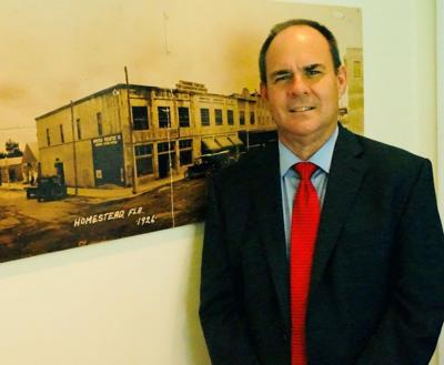 Steve Losner is a candidate for the mayor of Homestead.  Pictured here with a historic photo of Homestead circa 1926, hanging at City Hal