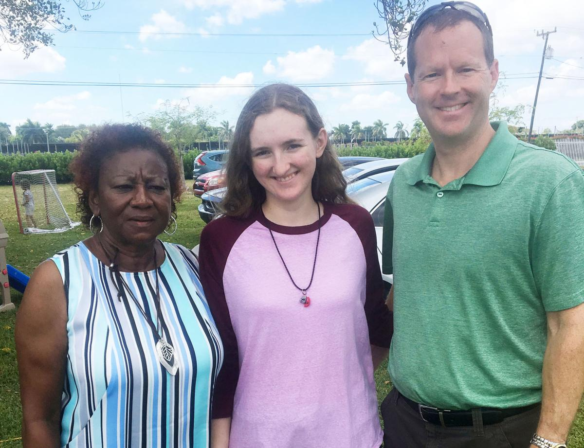 Julia Mitchell, of the Lamplighters Writer Group, left with contest winner Courtney Floyd and her father, Pastor Matt Floyd.