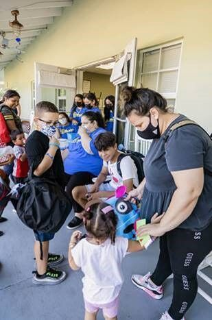 Students line up to pick up their backpacks filled with school supplies at Branches' Back to School Event on Aug. 19, 2021, in Florida City.