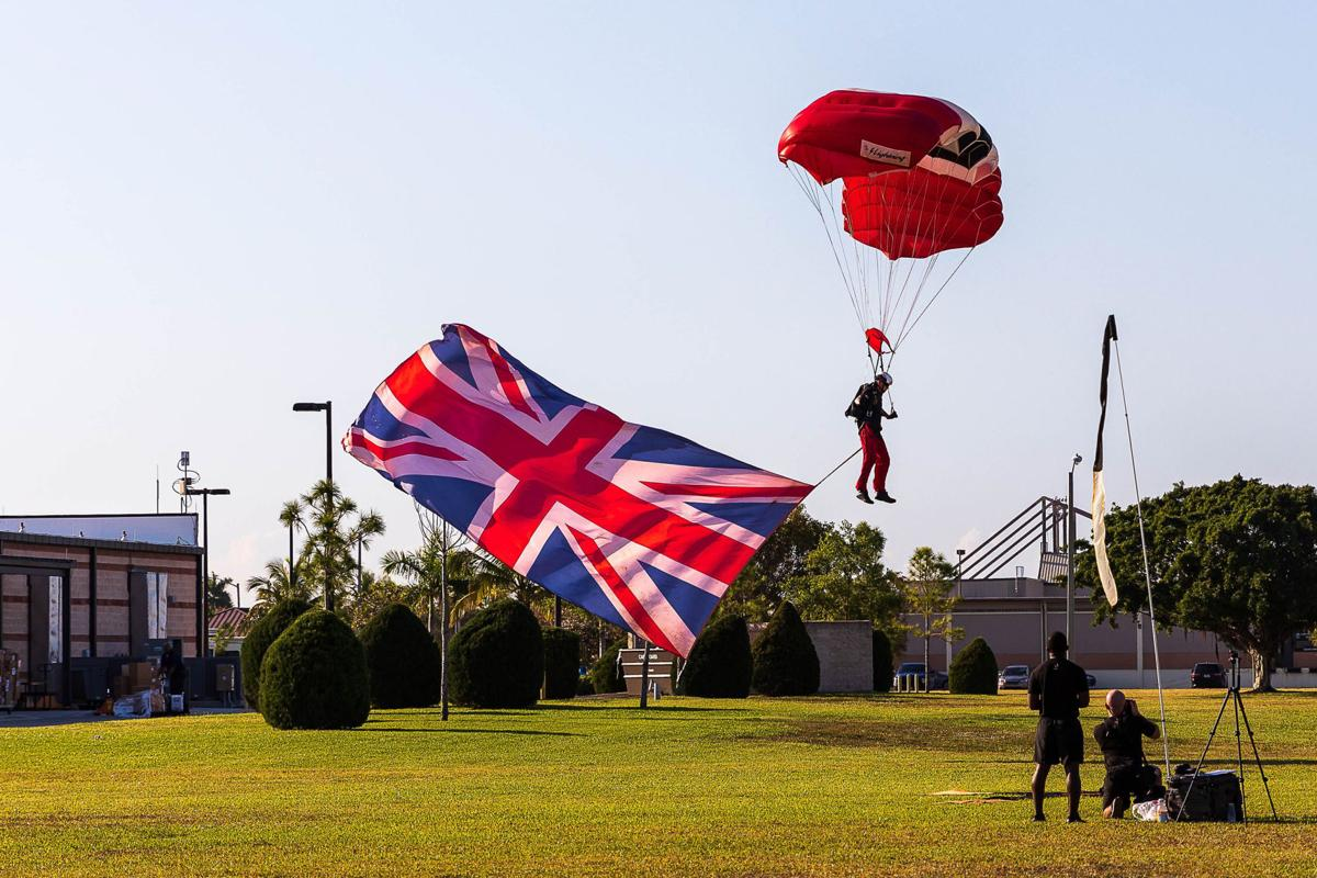 A member of the British Red Devils proudly jumps with their flag