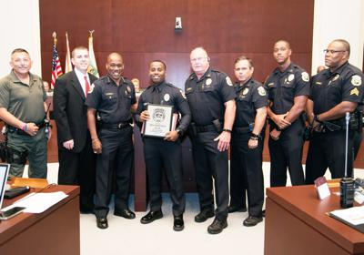Congratulating Officer Brandon Bowers (center, holding plaque) are from left:  Lt. Traad, Mayor Shelley,  Chief Rolle, Col. Kennedy, Capt. DeJohn, Capt. Wright, and Sgt. Guzman.
