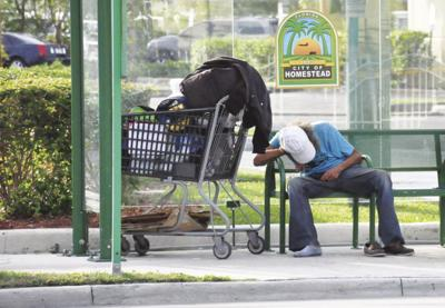 man with his possessions on a Krome Avenue bench.