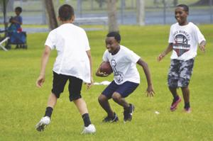 Local youth practice drills learned at the James Burgess Football Camp