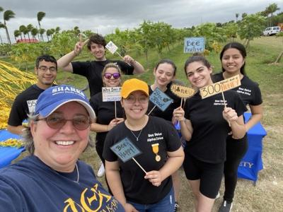 """Blanca Rosas is in the back right corner, holding the blue """"bee positive"""" sign as part of the Phi Theta Kappa-Homestead Campus Officer Team  of 2019-2020. They had a stand at Robert Is Here to raise awareness for their honors in action project, Saving the Bees."""