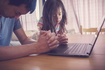 Child praying with father parent with laptop, family and kids worship online together at home, streaming online church service, social distancing concept