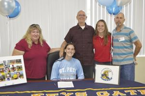 Keys Gate's Madison Wells is supported by her family as she signs her letter of intent to play softball at St. Petersburg College