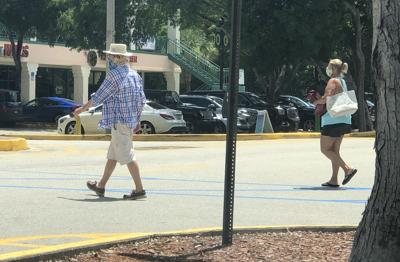 Customers outside of Publlix Key Largo put on their masks as they exit there cars to go shopping.