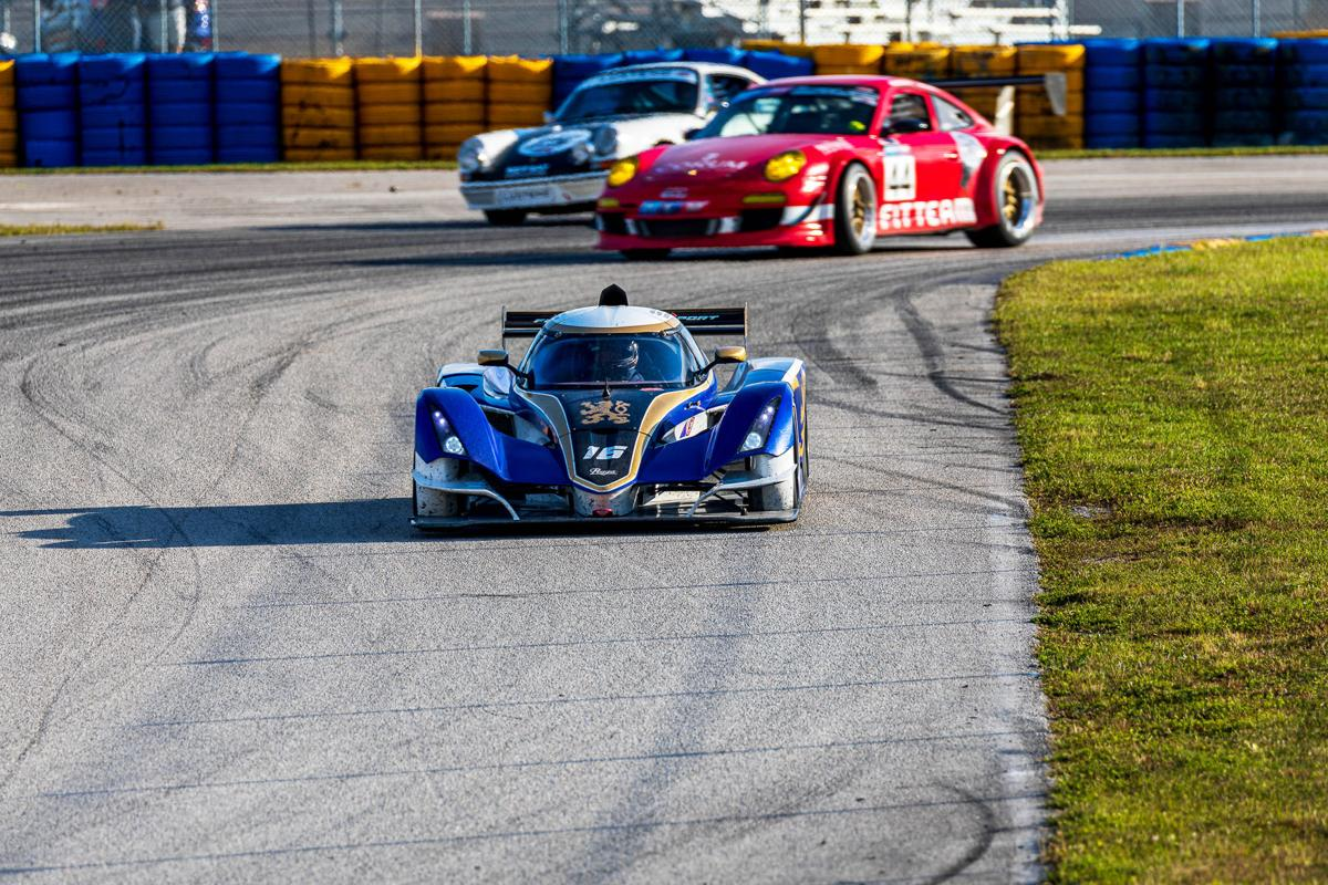 The #16 Praga R1T leads down the hill from Turn 3.