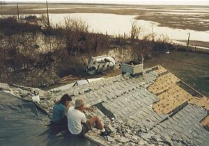 Danny Meneses and friend sit on the roof of the family home, surveying the damage.