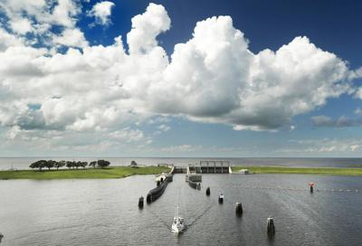 A sailboat starts down the St. Lucie Canal after leaving Lake Okeechobee, background, through the Port Mayaca, Fla., lock north of Belle Glade, Fla. The lock and dam was built in 1977 to raise the water level in the lake and provide flood control.