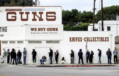 In this March 15, 2020, file photo, people wait in line to enter a gun store in California.