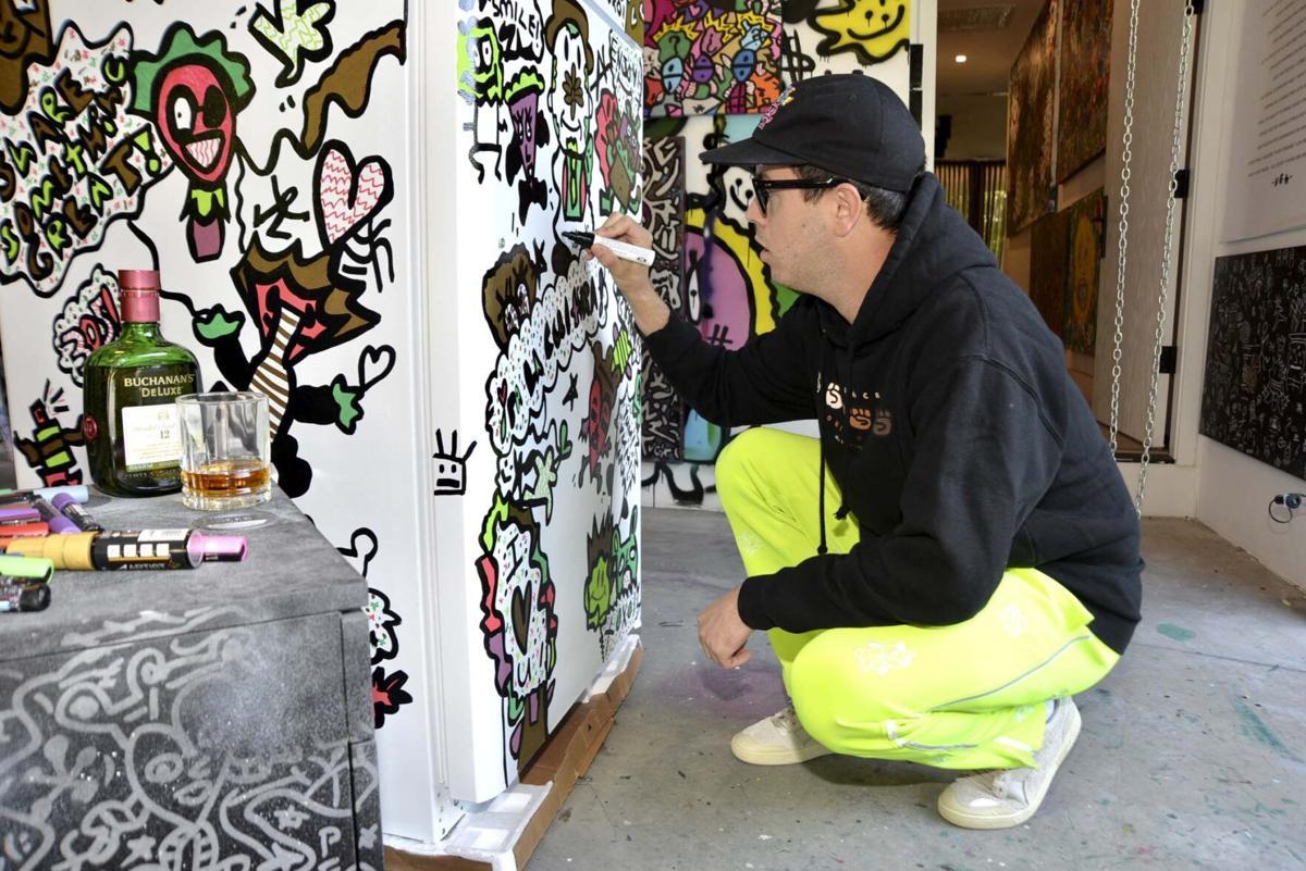 Artist Vic Garcia at work on a Community Fridge.